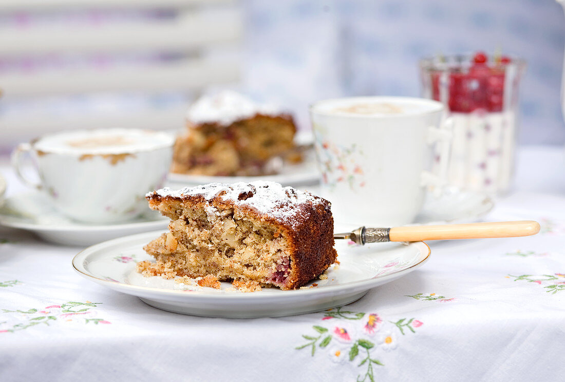 A piece of cake with an antique fork on an old floral china tea set with a matching tablecloth