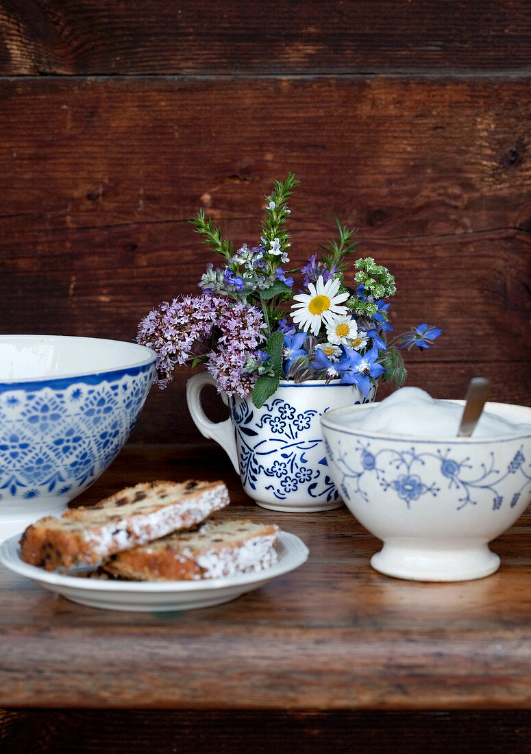 Posy of herbs in mug, sugar bowl and slices of cake