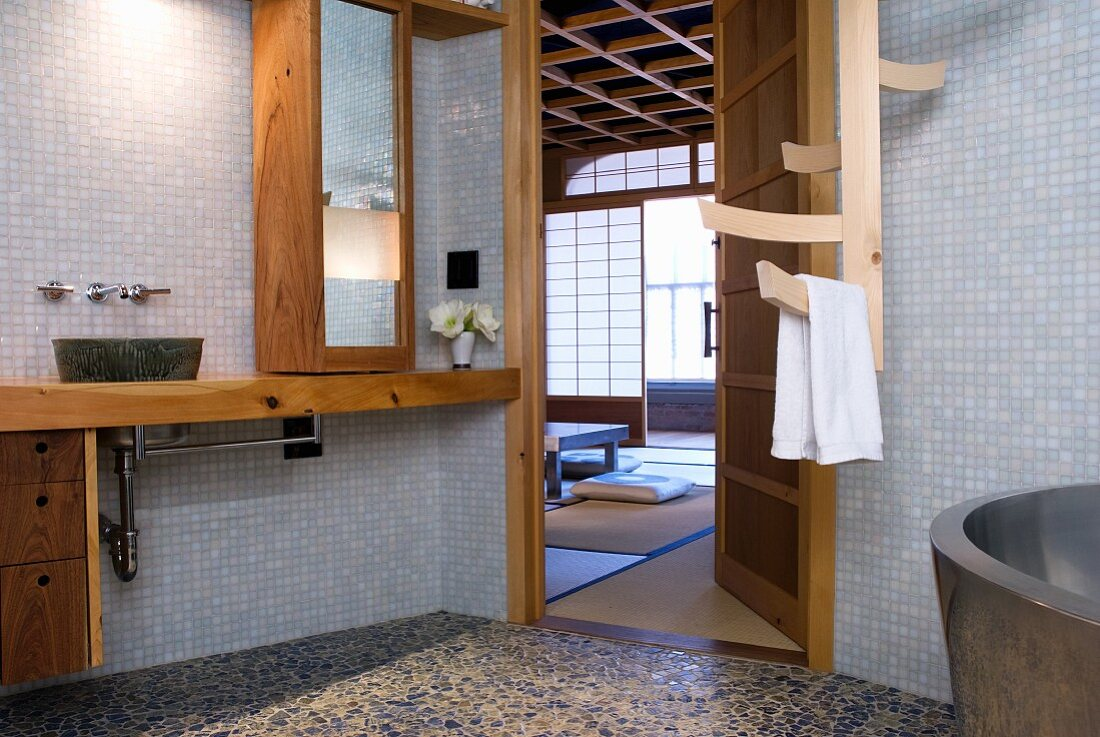 Simple bathroom with mosaic tiles on walls and wooden installations, open door with view of Japanese-style bedroom