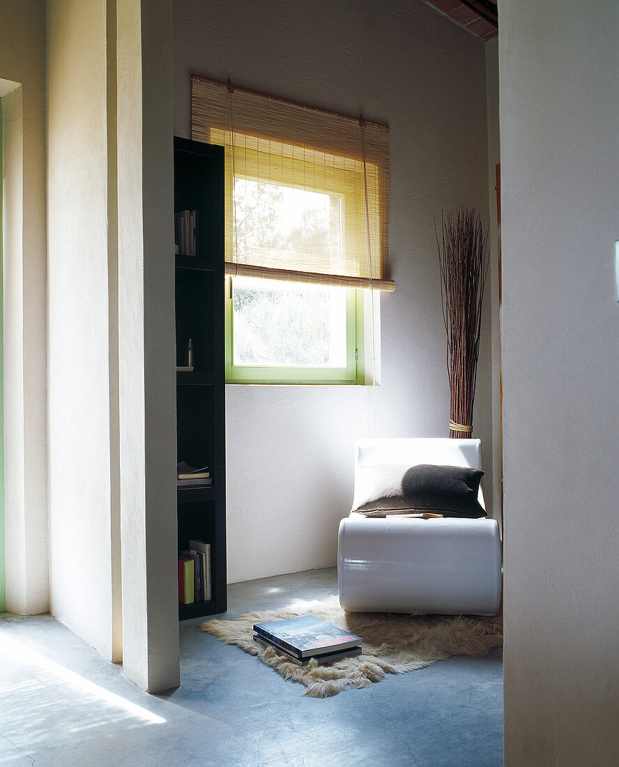 Modern, white reading chair in room in shades of blue with green window frame and half-closed blind