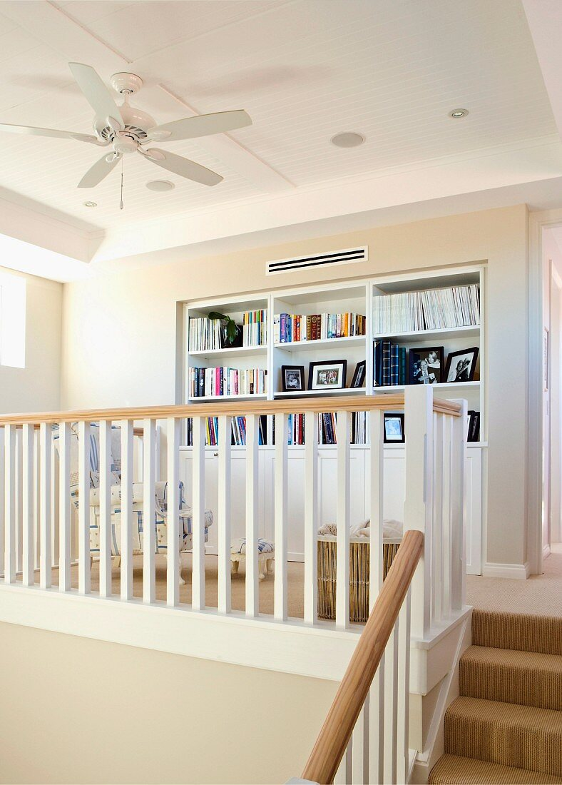 Cosy library on gallery with fitted shelving, wooden balustrade and ceiling fan
