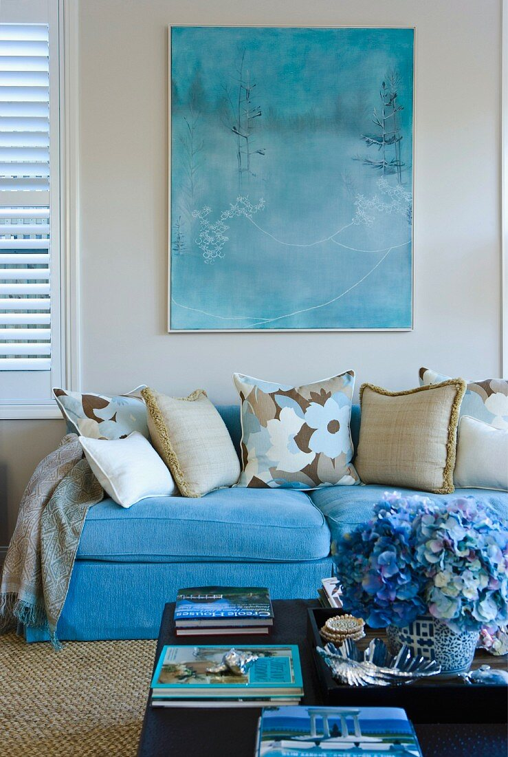 Turquoise couch below watercolour in the same shade; bouquet of blue hydrangeas on coffee table in foreground
