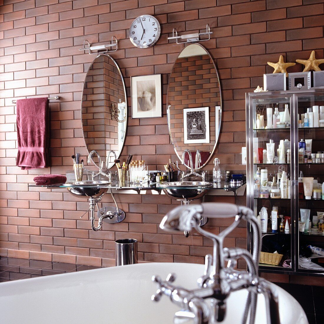 Vintage style bathroom - partially visible bathtub with vintage tap fittings and modern washstand with oval mirrors on brick-effect wall