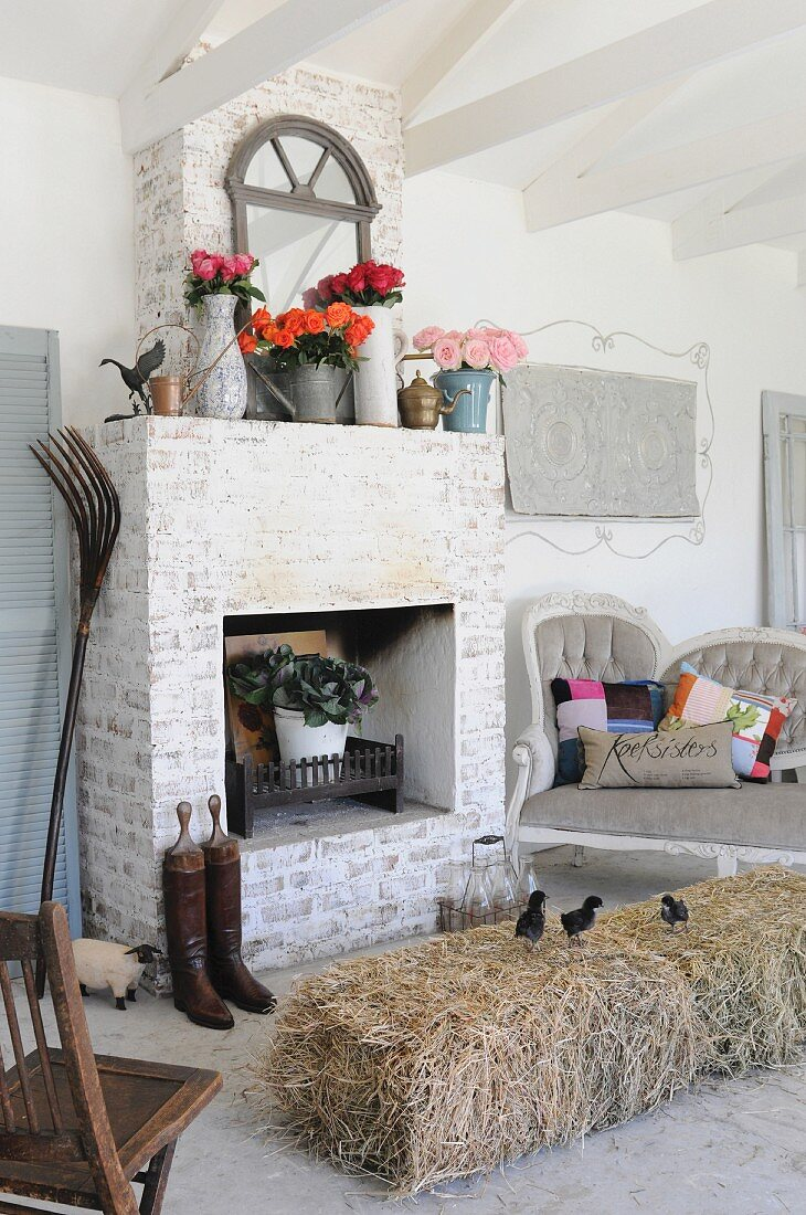 Living room with bale of hay serving as a table and brick-built fireplace