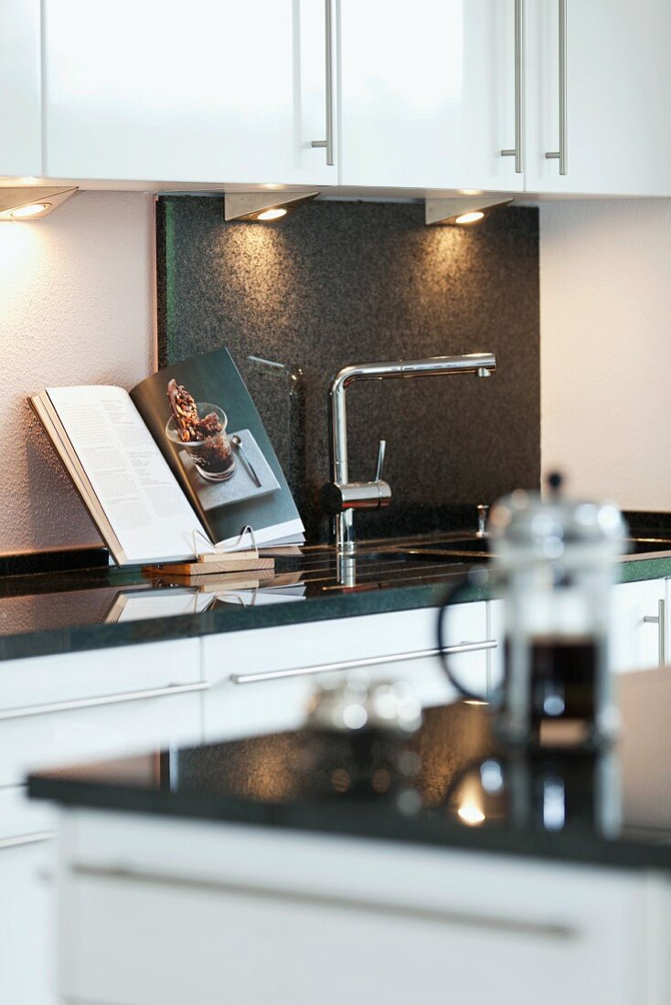 Kitchen counter with sink and open cookery book