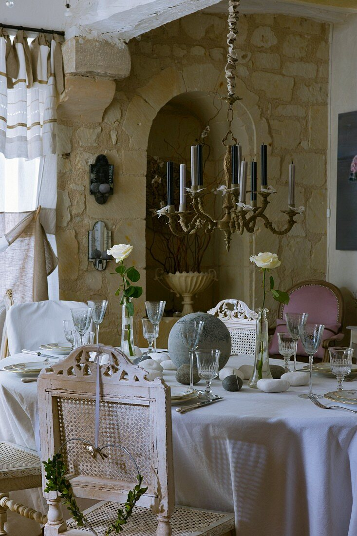 Brass chandelier above festively set table with antique, white, vintage-look chairs; stone wall in background