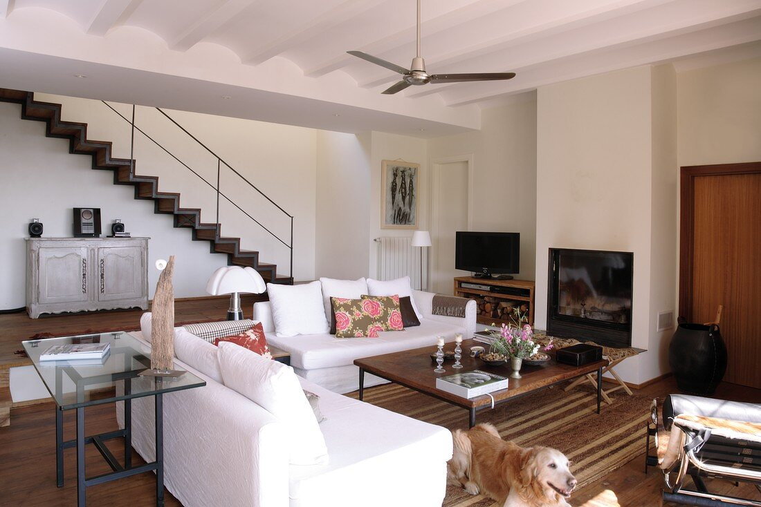 White sofa set below Mediterranean ribbed ceiling with fan and open-plan interior staircase in background