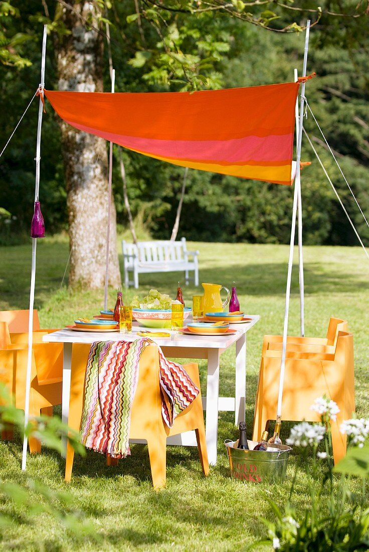Brightly coloured, hand-sewn awning on white-painted bamboo canes above summery set table in garden