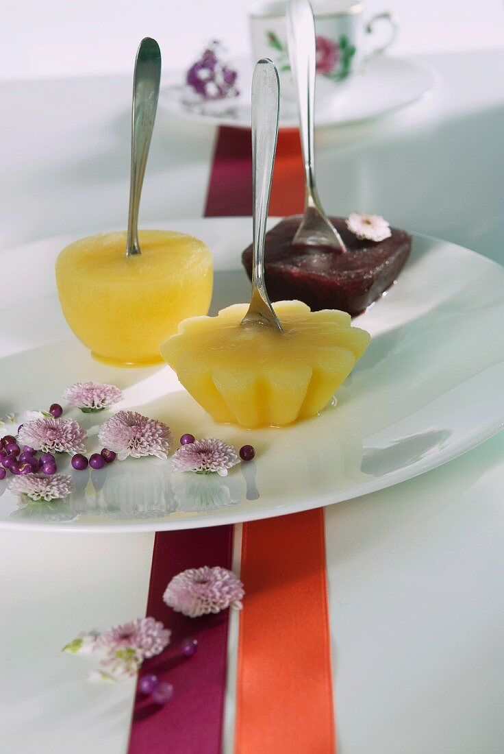 Fruit sorbets on a plate with spoons for sticks