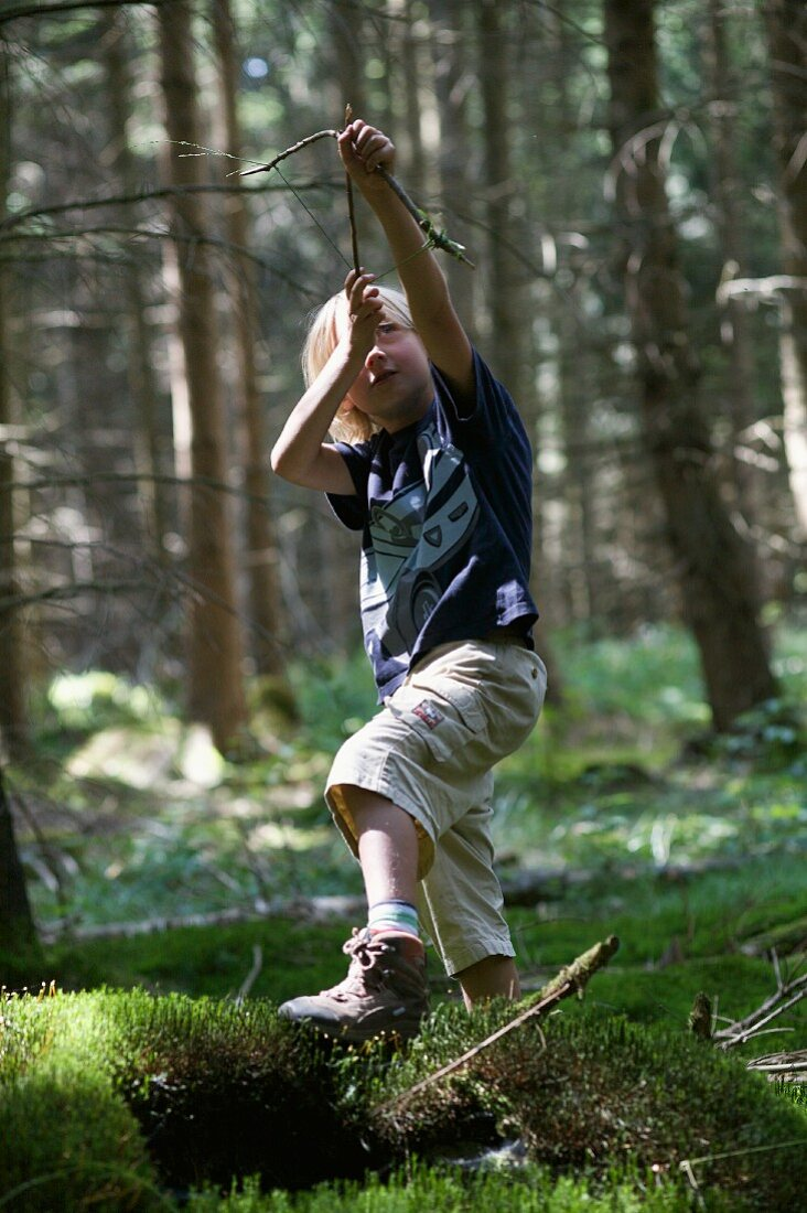 Boy playing in woods