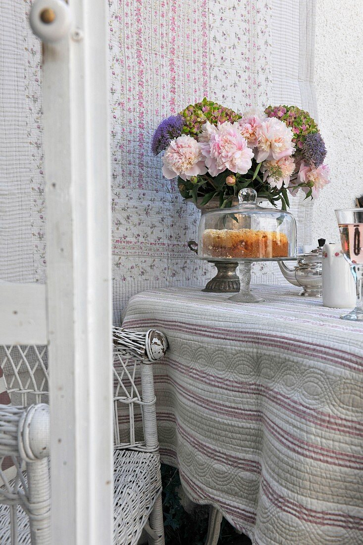Cake under glass cover and vase of flowers on table covered in ethnic throw with wall hanging in background