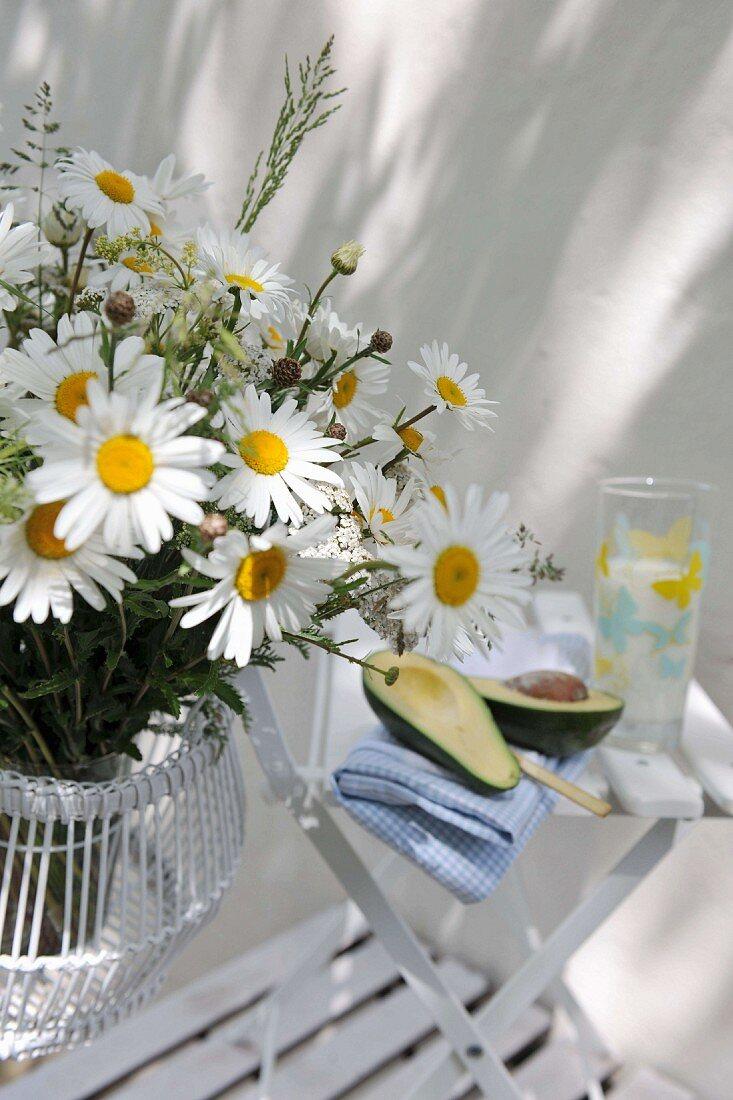 Bouquet of ox-eye daisies next to cut avocado on garden chair