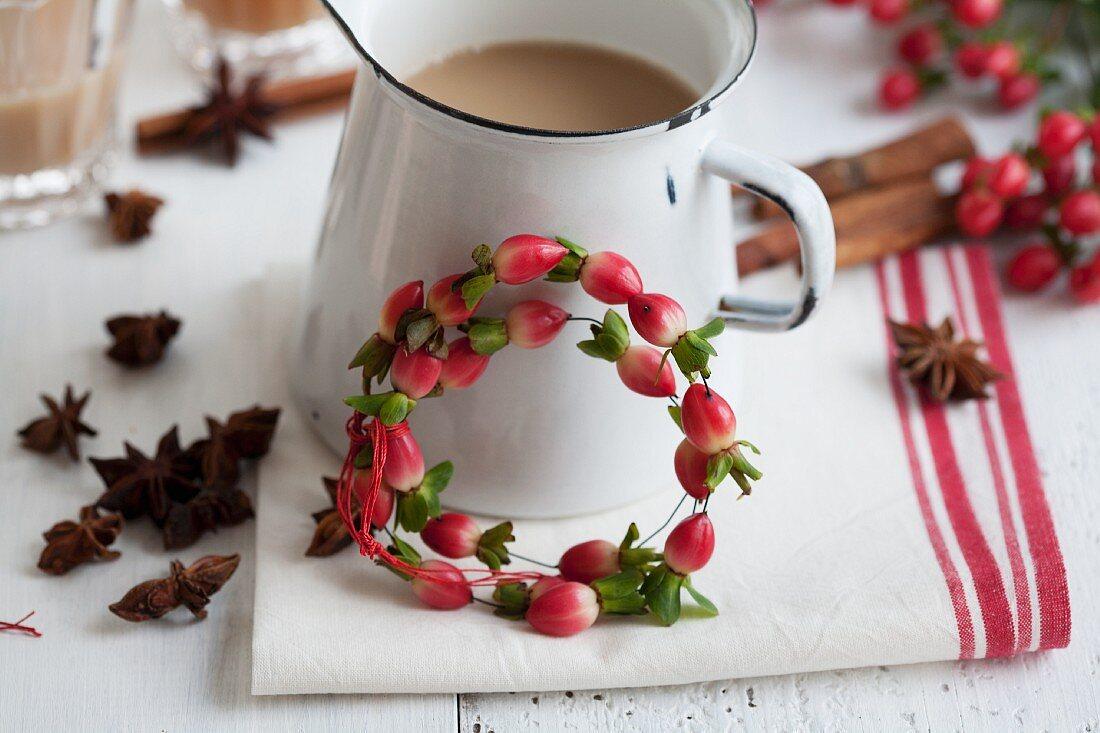 Kanne mit Chai-Tee und Kränzchen aus Johanniskrautbeeren