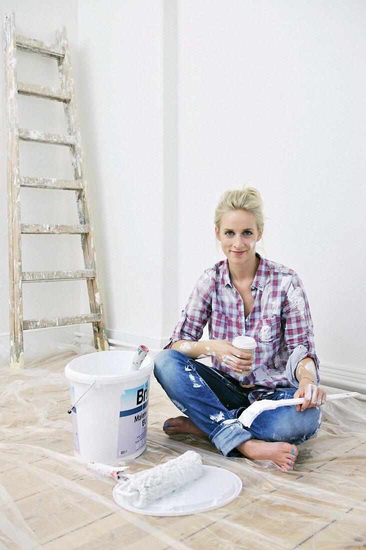 Renovierungsarbeiten - Frau macht eine Pause