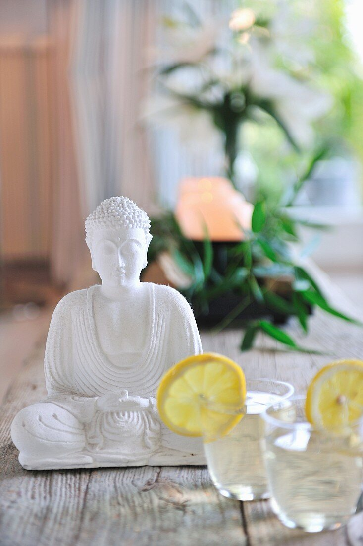 Refreshing drinks next to seated Buddha figurine in white stone on wooden floorboards