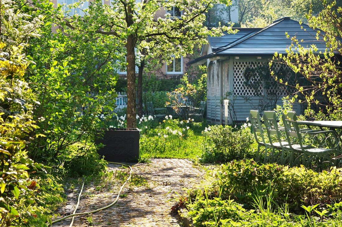 Spring day - seating area on terrace in front of wooden summer house in blooming garden