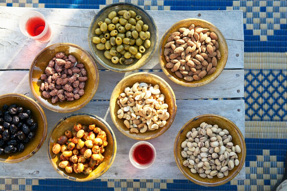 Dishes of Oriental nibbles on rustic wooden table