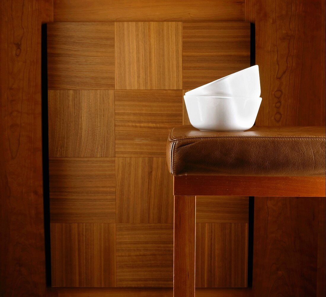 Two white bowls on bar stool against brown wooden wall