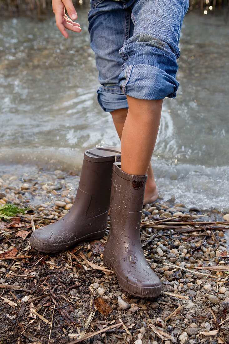 Girl taking off rain boots by pond