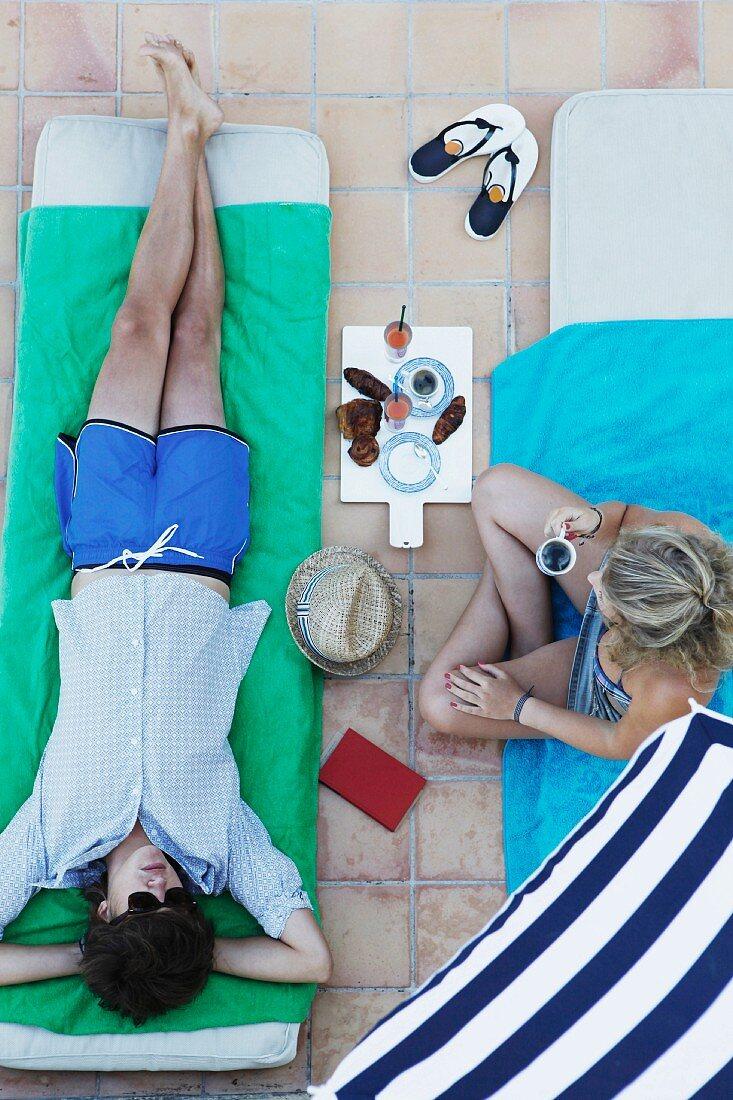 Couple relaxing on beach mats