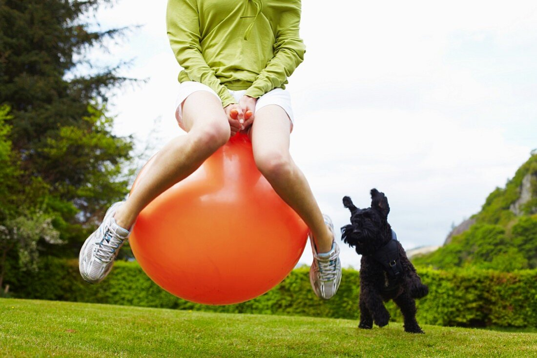 Woman on bouncy ball playing with dog