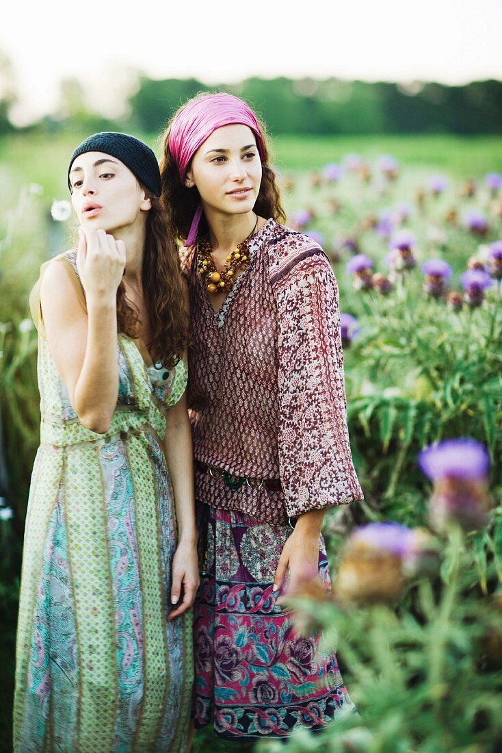 Young hippie women standing in field, one blowing dandelion seeds