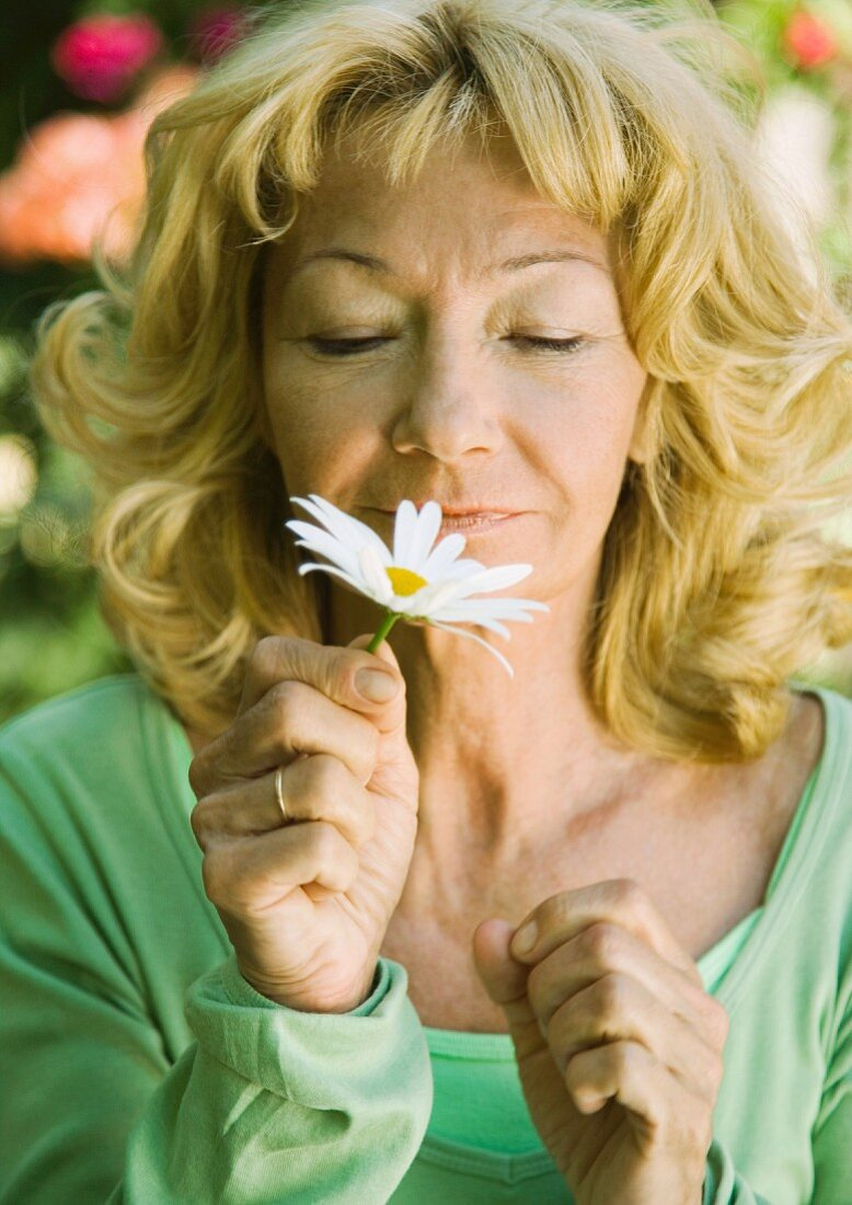 Senior woman smelling daisy