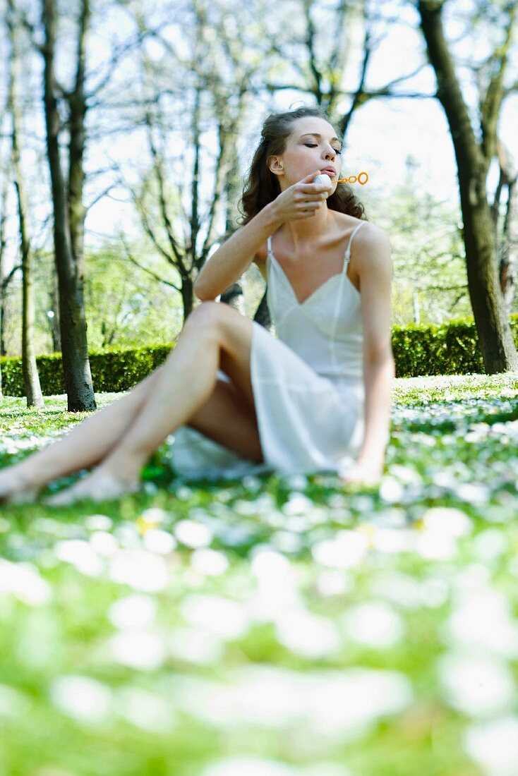Young woman wearing slip, sitting in field of flowers, blowing bubbles
