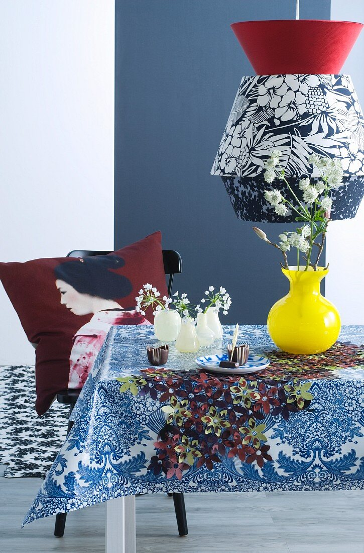 Black and white pendant lamp with floral pattern above dining table and Geisha cushion on chair