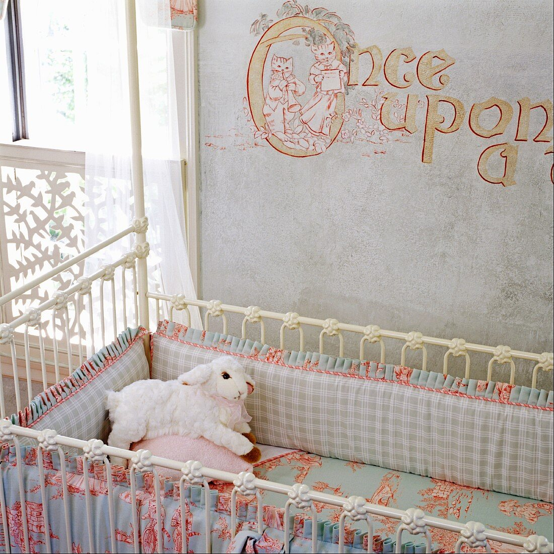Antique, white cot with pastel bed linen against wall painted with lettering
