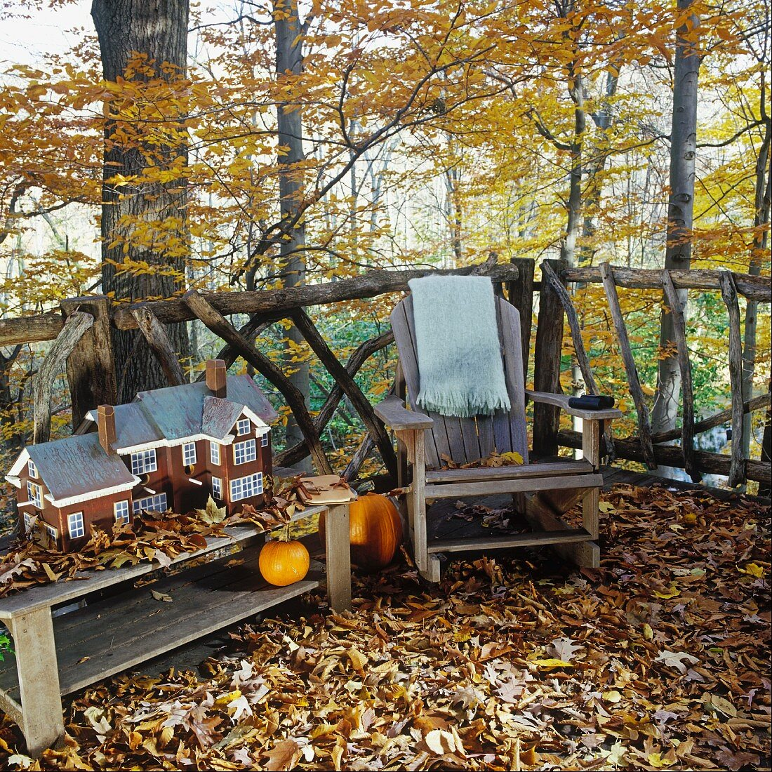 Autumn terrace carpeted with leaves with rustic armchair and model of house on wooden table