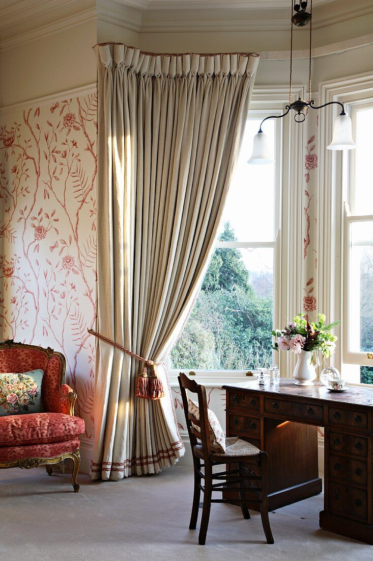 Antique desk in bay window with gathered curtains in traditional setting