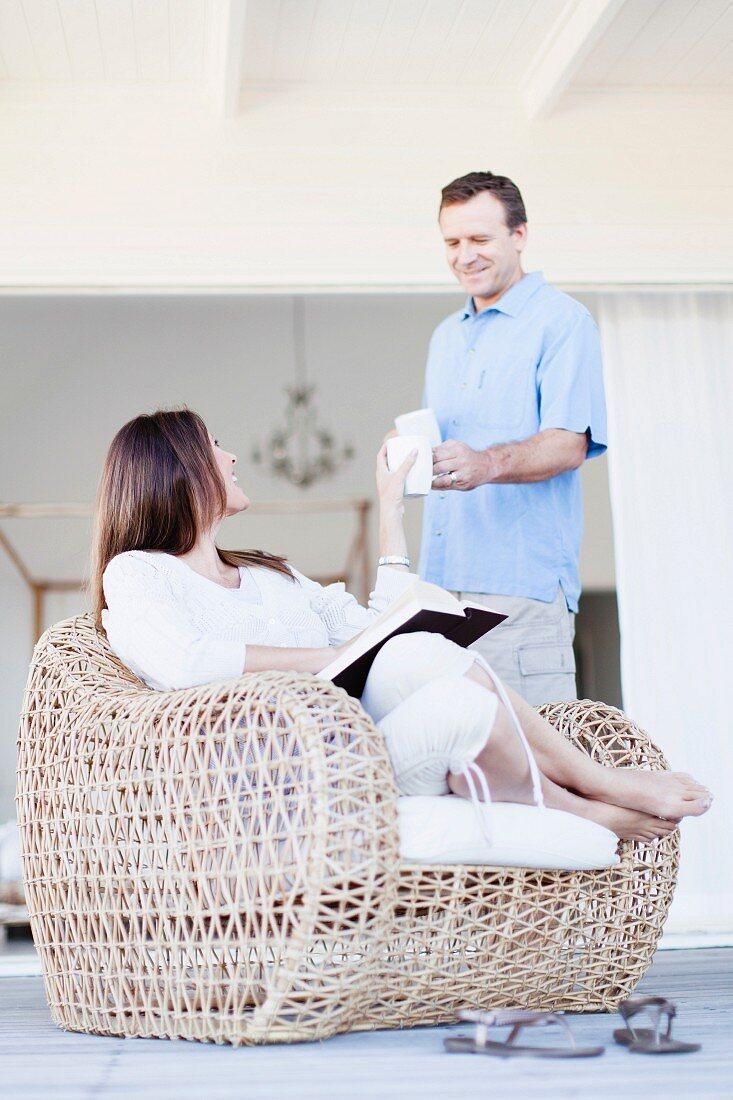 Brünette Frau sitzt in einem Korbsessel, Mann steht neben ihr mit Tasse