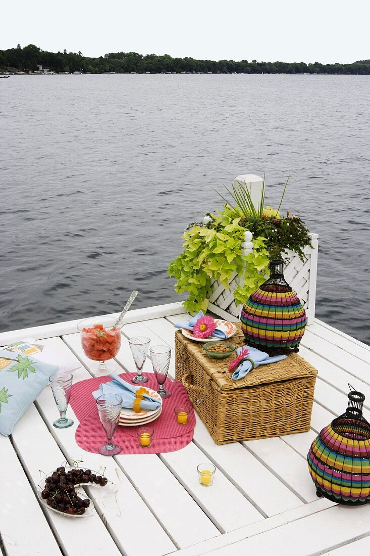 Picnic preparations on white-painted wooden jetty on lake shore