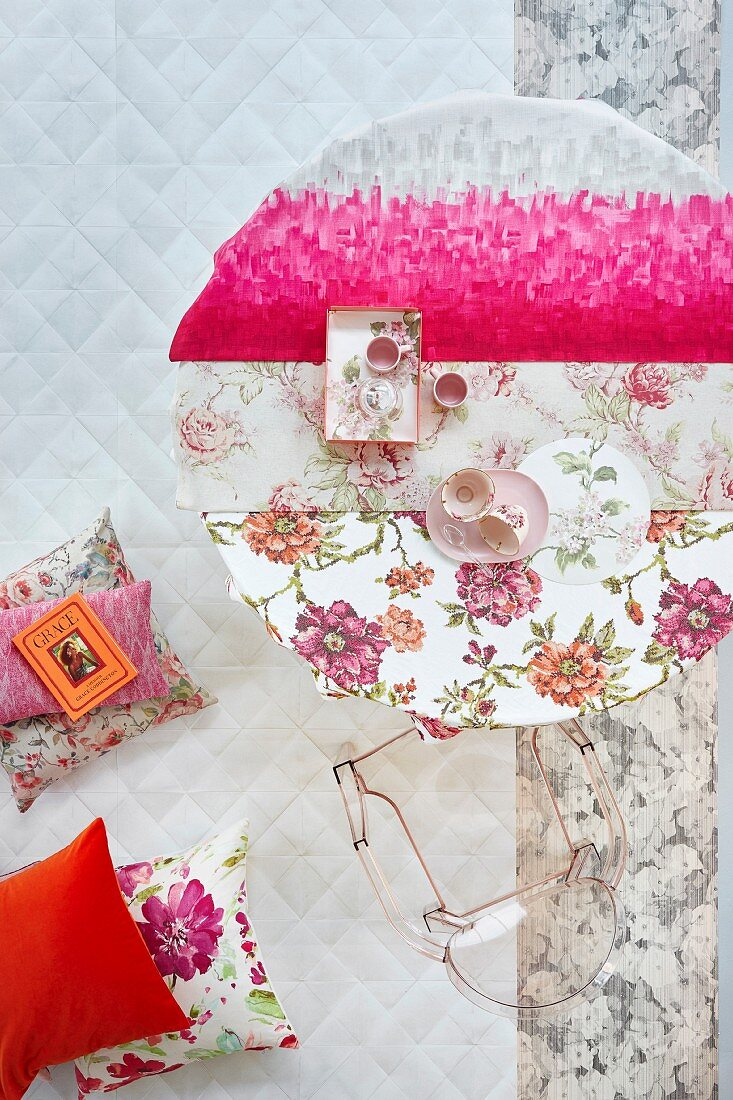 Kräftiges Pink als moderner Akzent zu Decken mit femininen Blütenmustern auf einem rundem Tisch