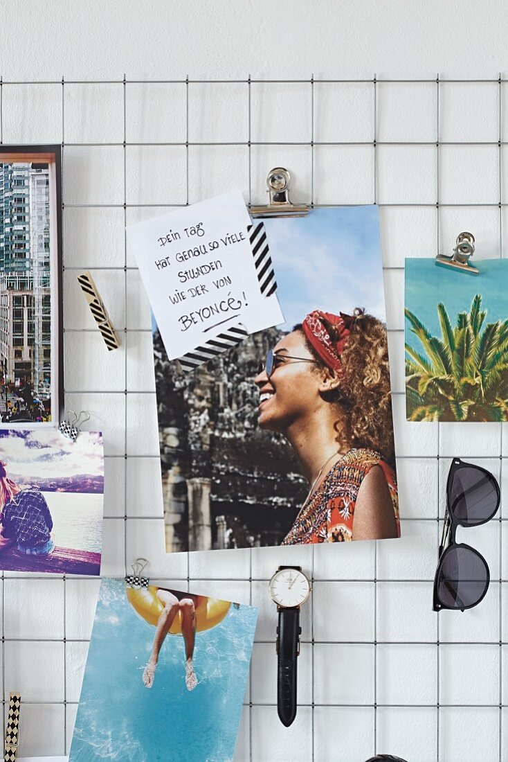 Postcards, quotes, a watch and a pair of sunglasses on a wire noticeboard