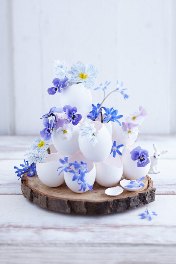 A pyramid of egg shells filled with blue spring flowers on a slice of bark