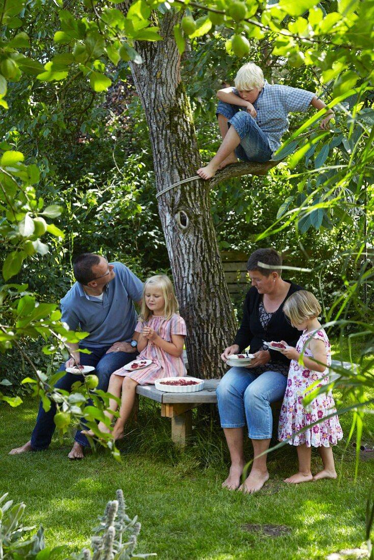 Family eating fruit tart under tree in garden