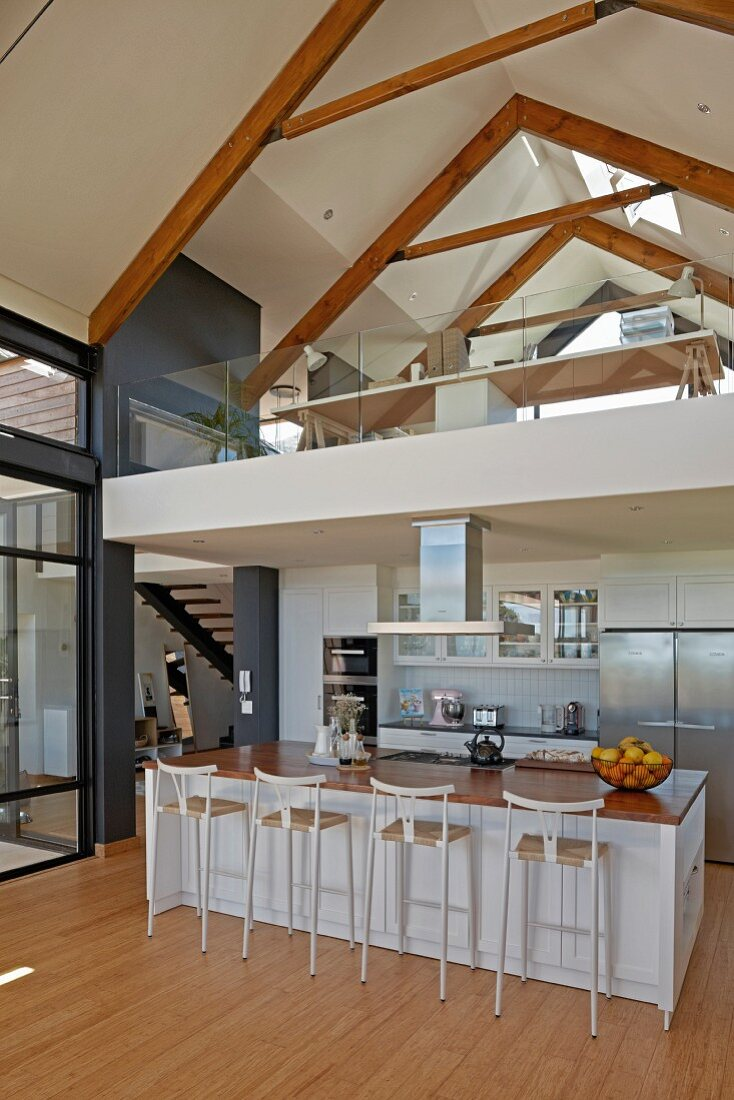 Open-plan kitchen with bar stools at counter below gallery in contemporary interior