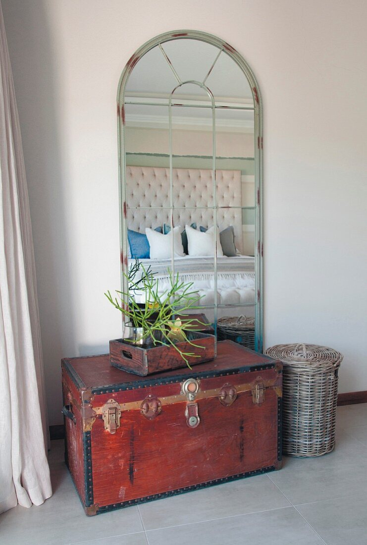 Old trunk in front of latticed arched mirror in bedroom