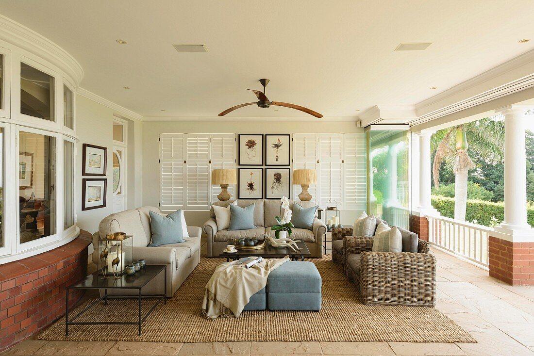 Comfortable seating area with sofas, ottomans and sisal rug on tiled floor of roofed veranda