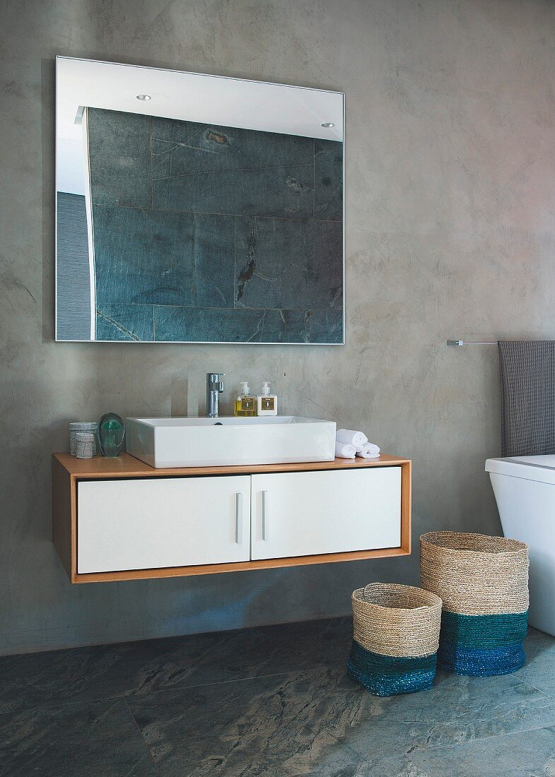 Floating washstand and seagrass baskets against concrete wall and below mirror reflecting slate tiles