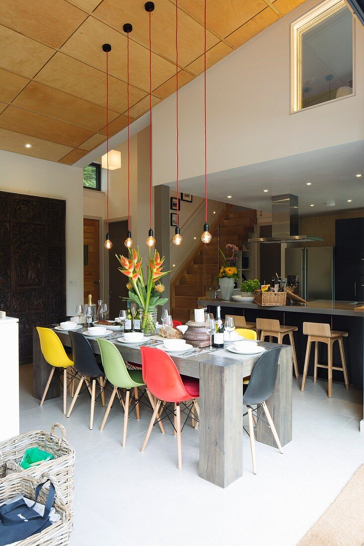 Colourful classic-style shell chairs around set table below simple light-bulb pendant lamps; bar stools at counter in background