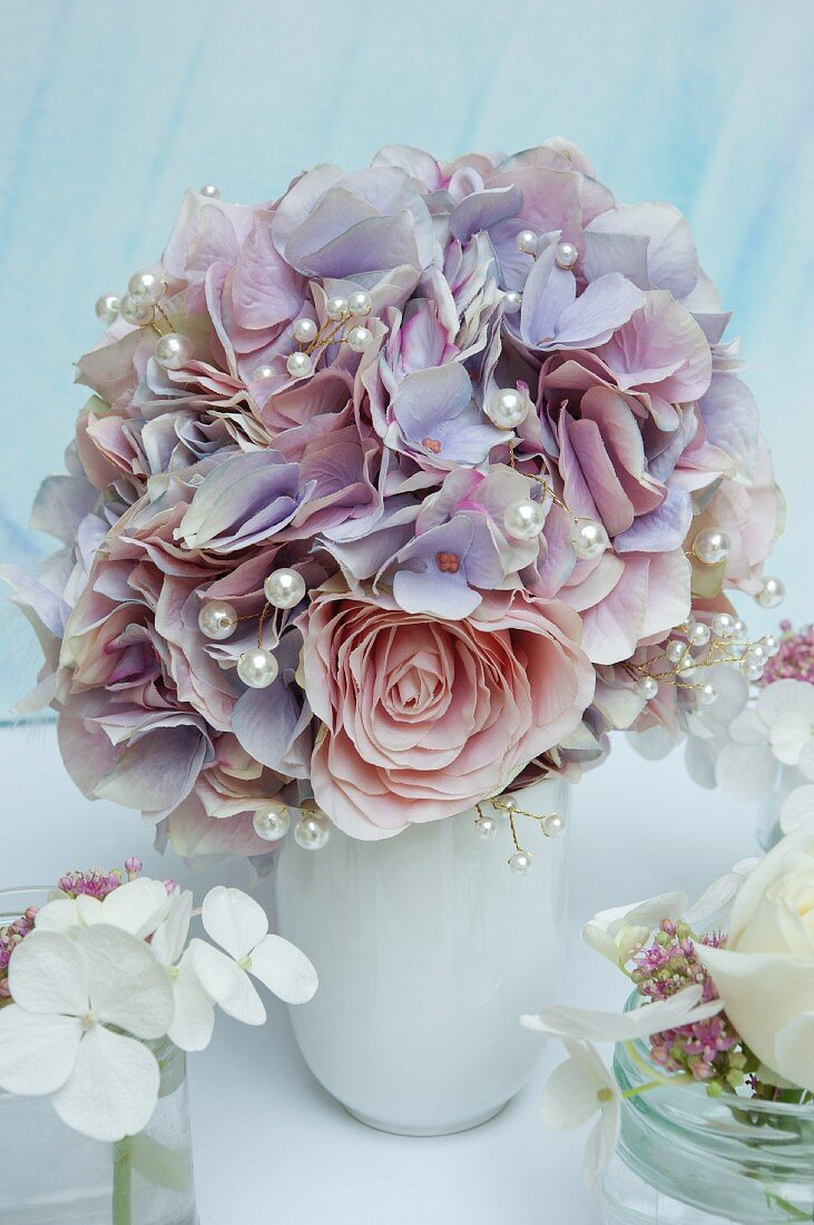 Elegant bouquet of silk flowers decorated with white pearl beads