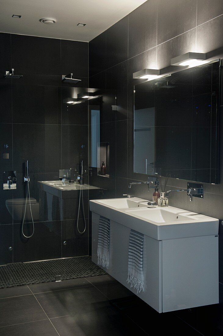Washstand with white base cabinet against black-tiled wall below wall lamps above mirror in designer bathroom