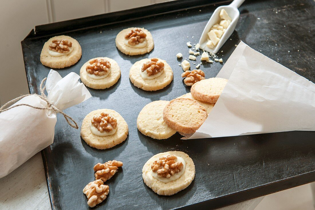 Christmas biscuits topped with walnuts on baking tray