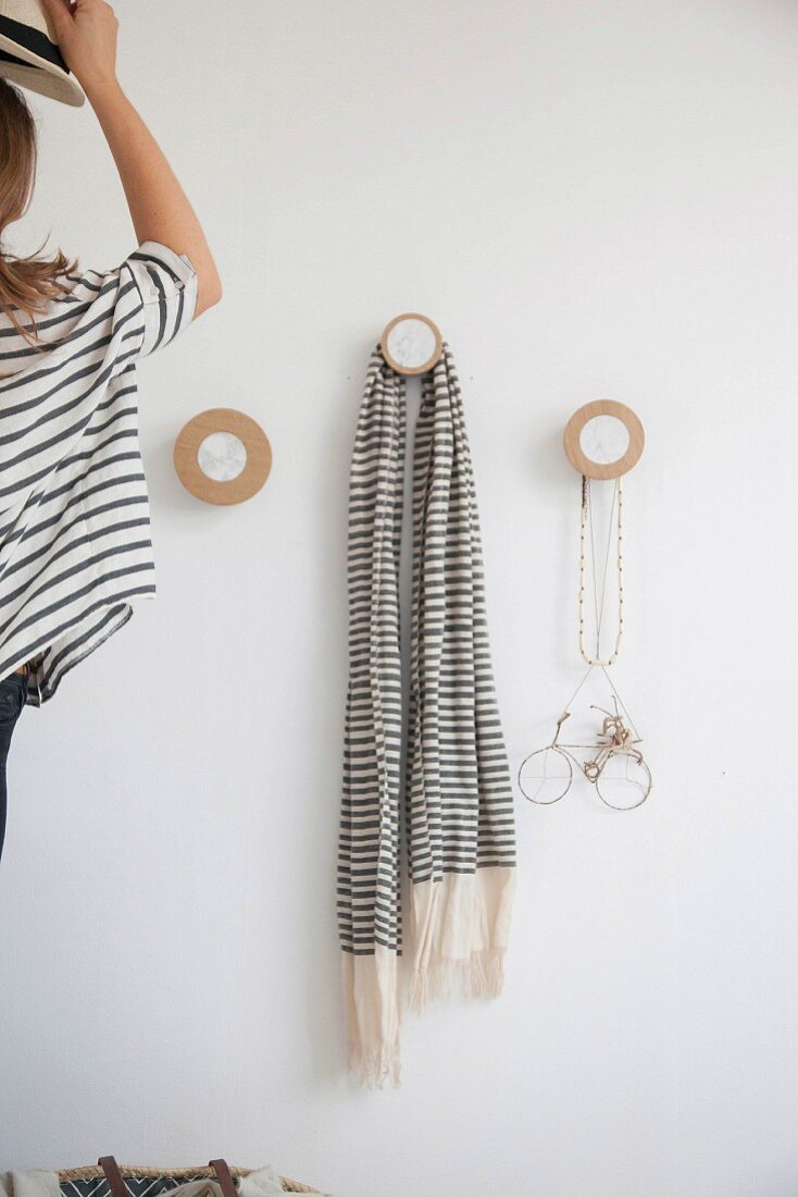 Woman hanging hat on coat pegs made from round wooden discs