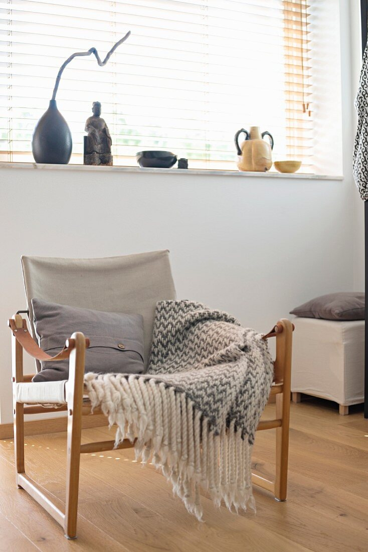 Armchair with wooden frame, linen seat and grey and white fringed blanket below window