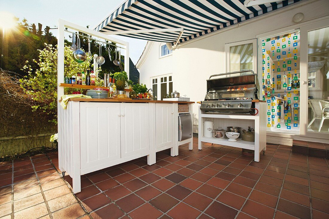 White-painted base units on tiled summer terrace with DIY outdoor kitchen