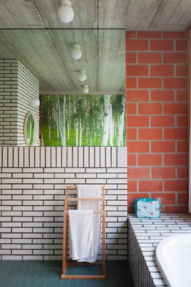 Bathroom with brick wall and concrete ceiling in industrial loft apartment